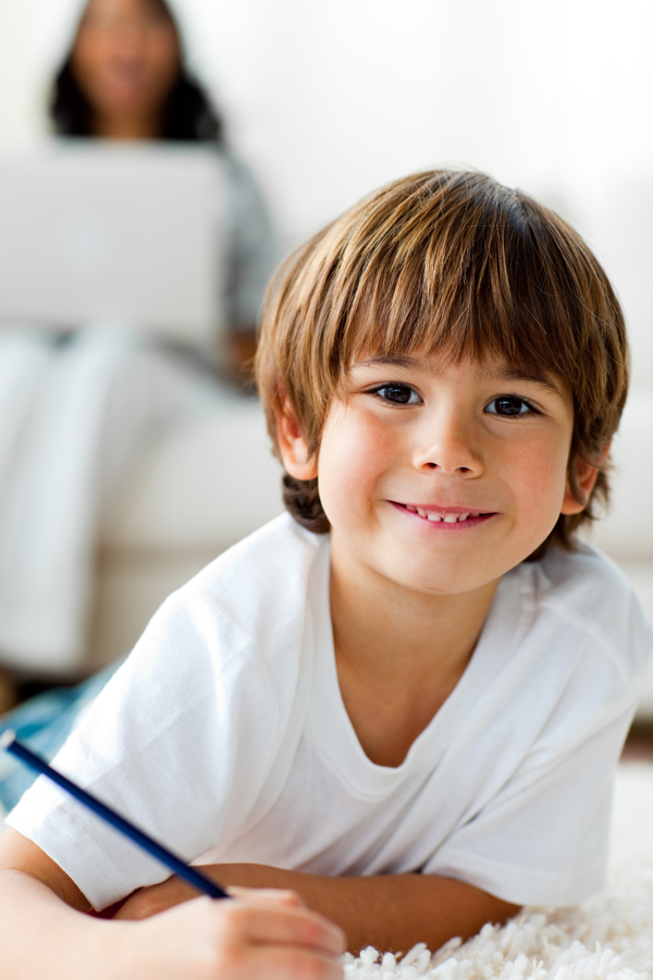 young school boy smiling and writing