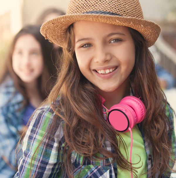 Young girl smiling with pink headphones around her neck.