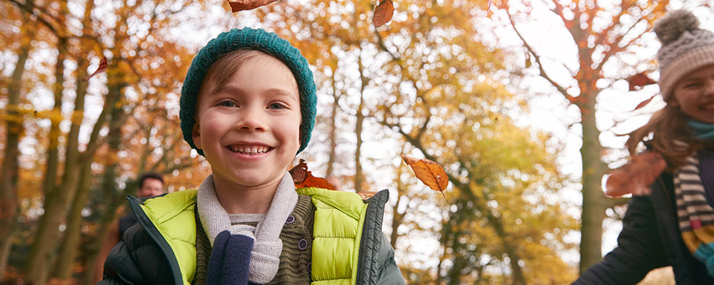 Smiling child in the woods in fall
